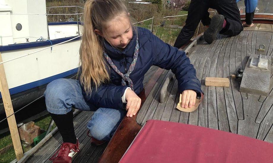 Marie på ti år hjælper til med at slibe dækket. Foto: Malene Wilken