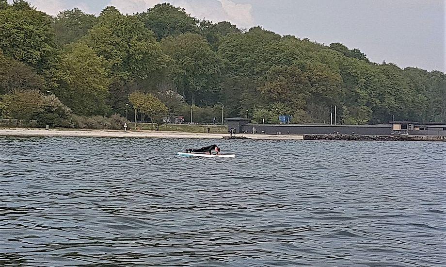Politiet fik flere anmeldelser om voldsom sejlads ved den populære badestrand. Her ses imidlertid en fredelig SUP-sejler, der tager armbøjninger. Foto: Troels Lykke